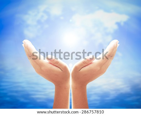 Human open empty hands with palms up over blurred world map of clouds and beautiful nature background. World Environment Day concept. Pray for support concept. Business concept. Dignity concept.