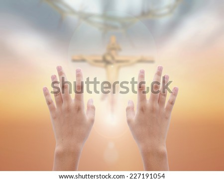 Human raising two hands over blurred crown of thorns and Jesus with the cross on a sunset. - stock photo