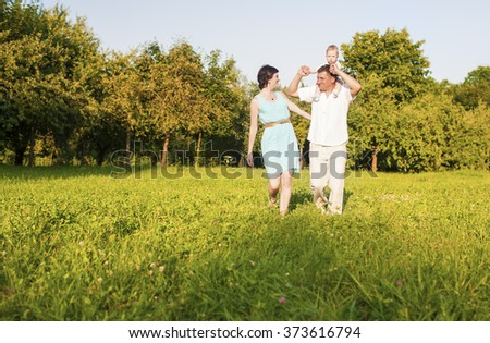 Human Relationships Concepts. Young Caucasian Family of Three People Having Good Time Together Outdoors.Horizontal Image - stock photo