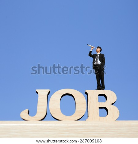 Human resource concept - business man stand on JOB text word with telescope ( spyglass ) and look for job - stock photo