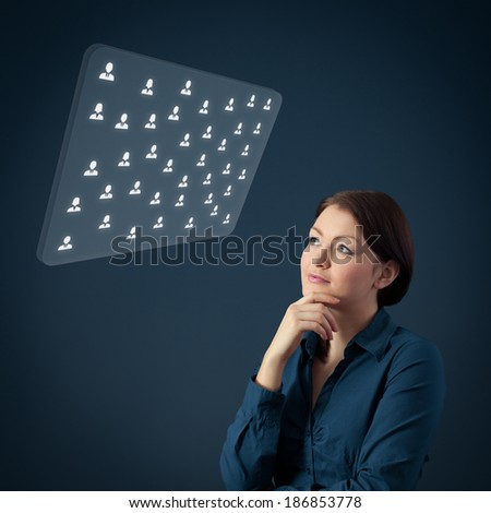 Human resources female officer think about new candidates or team structure displayed on futuristic virtual screen. Marketing specialist think about customers.