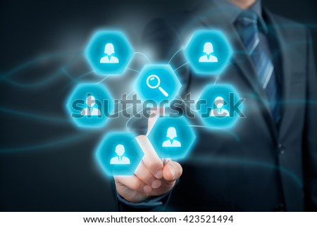 Human resources officer looking for (search) employees. Businessman click on loupe (magnifying glass) to find the best employee for his team. - stock photo