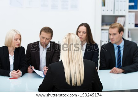 Human resources team conducting an interview reading the credentials of a blond business applicant sitting with her back to the camera - stock photo