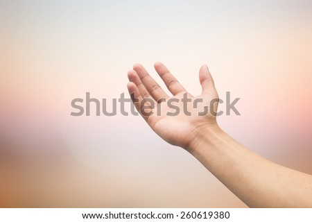 human right hand with empty on blurred twilight sky backgrounds with selective focus:blessing and forgiveness concept.prayer and powerful conceptual.soft focus. - stock photo