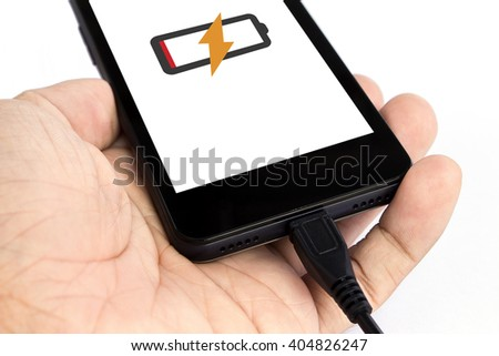 human's hand holding smart phone is charging on white background