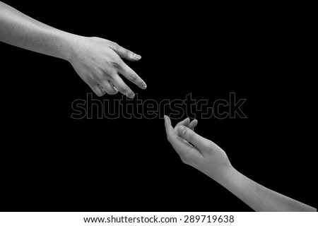 Human's hands help together isolated on black backgrounds.helping hand concept,black and white hands concept. - stock photo