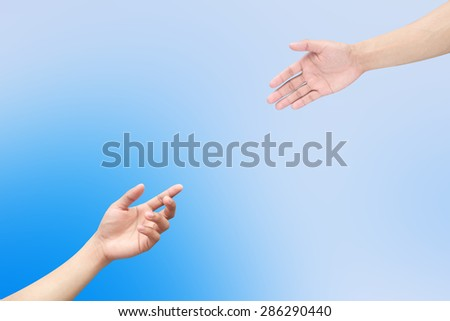 Human's hands help together on blurred blue sky  backgrounds.helping hand concept. - stock photo