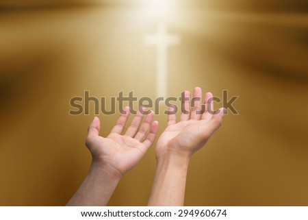 human's hands pray cross on blurred tan brown sepia background with rays beam light :man hand open palm up for receiving power from god.religion concept.faithful people ideal:strength and force. - stock photo