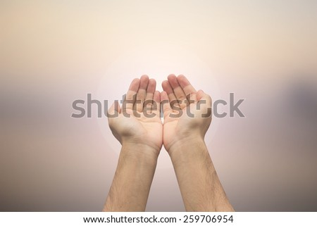 Human's hands pray on blurred nature background