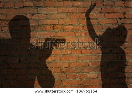 Human silhouette with handgun in shadow on brick wall background