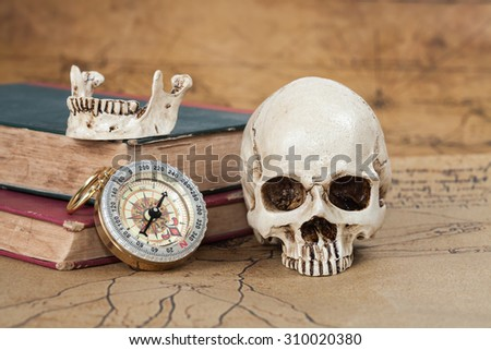 Human Skull and compass on Old map Background - stock photo