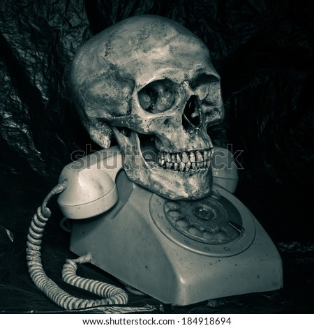 Human skull model with old telephone