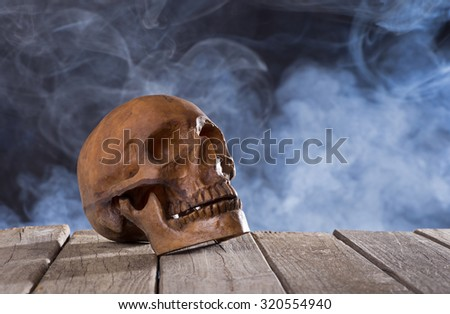 Human skull on wood boards with smoky background - stock photo