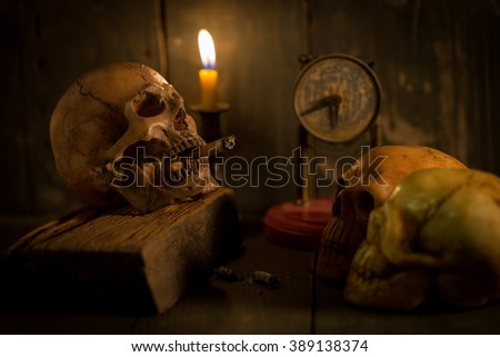 Human skull smoking a cigarette,old watch and candle ,No smoking campaign ;still life