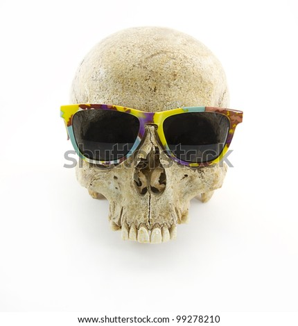 Human skull wearing a colorful sunglasses over monochrome white background - stock photo
