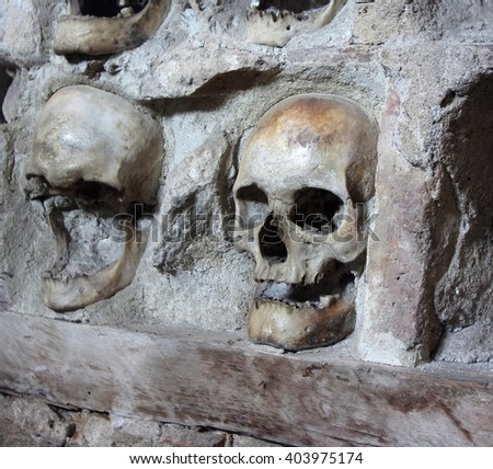 Human skulls embedded in the wall as a part of an ancient monument. - stock photo