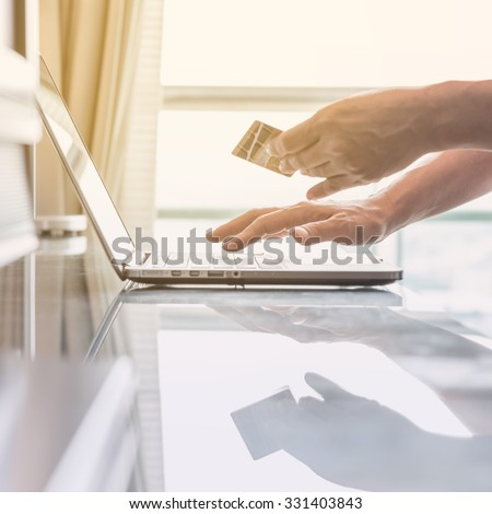 Human woman hand holding credit card while using computer for internet product ordering/ online shopping/ banking tele-booking: Buyer/ customer typing credit card number order goods from home: PPC IM