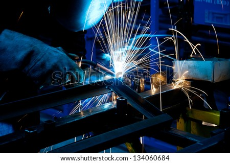 human working of welding with a lot of sparks in a metal industry factory - stock photo