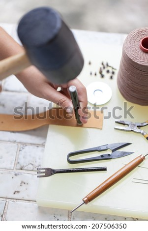 human working on leather - stock photo