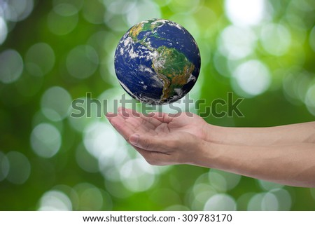 humans hand open palms gesture for show world over blurred green nature backgrounds : human hand safe world life concept,ecology concept.Elements of this image furnished by NASA. - stock photo