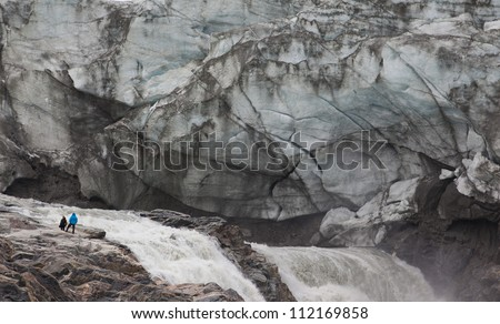 Humans in front of melting glacier, Kangerlussuaq, Greenland - stock photo