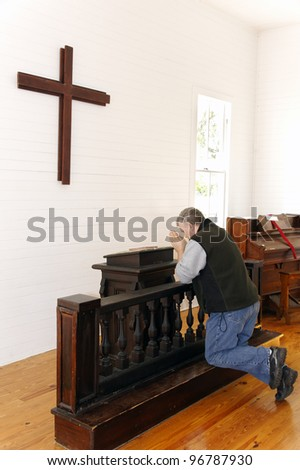 Humble man kneeling and praying in a church with a cross and piano. - stock photo