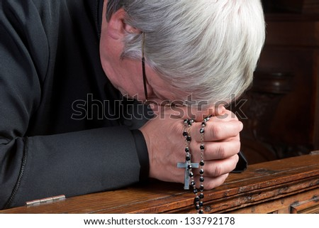 Humble priest kneeling down and praying with his rosary - stock photo