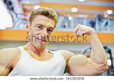 Humeral portrait of smiling bodybuilder who demonstrates tensed biceps - stock photo