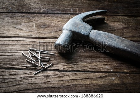 Hummer and nails on wooden background - stock photo