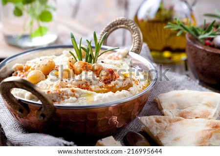 Hummus, chickpea dip, with rosemary, smoked paprika and olive oil in a metal authentic bowl with pita on a wooden background.  - stock photo