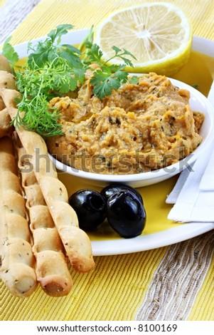 Hummus dip served with lemon, cilantro or coriander, black olives and bread sticks. - stock photo