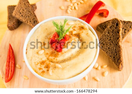 Hummus in a bowl with vegetables (red pepper) pine nuts and bread, close-up, horizontal - stock photo