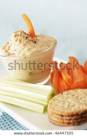 Hummus in a clear bowl with vegetables and cracker in a white plate - stock photo