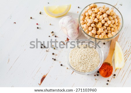 Hummus ingredients - chickpea, lemon, garlic, sesame, oil, pepper, parsley, white wood background, top view - stock photo