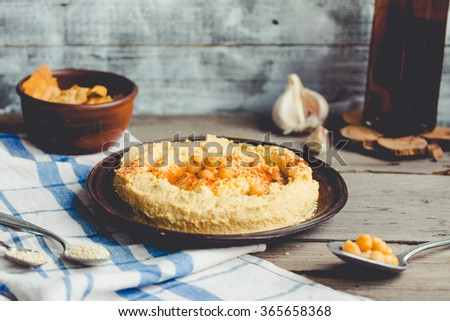 hummus of chickpeas, tahini paste and with paprika,vegan snack,Rustic background - stock photo