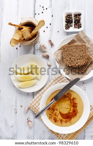 hummus, rye bread and turkish crisps on white distressed table - stock photo