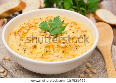 Hummus with pine nuts in a bowl, close-up, horizontal