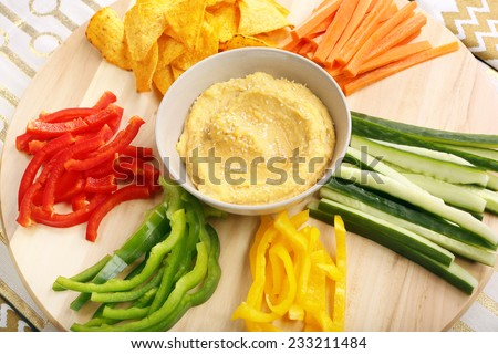 Hummus with vegetables on a wooden swivel table - stock photo