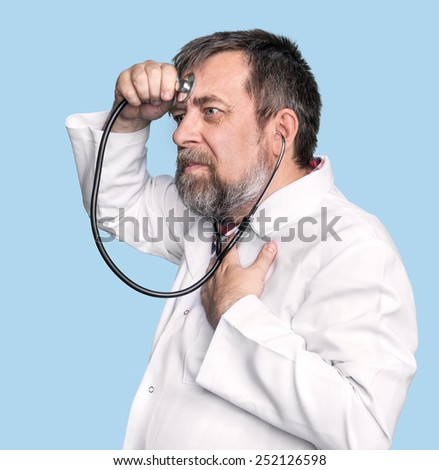 Humorous concept of health. Mad doctor with a stethoscope isolated on blue - stock photo