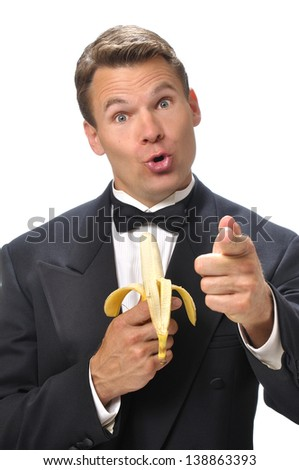 Humorous handsome Caucasian man in black tuxedo holds banana microphone and points finger at camera with white background