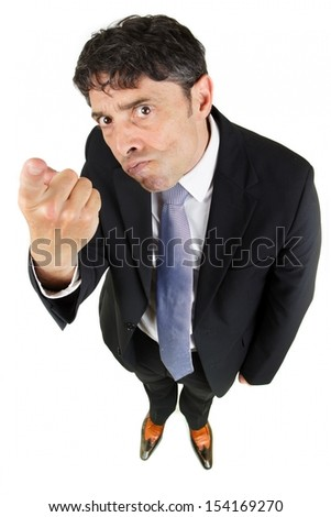 Humorous high angle portrait of a man in a business suit pointing a finger in accusation and blame with a stern uncompromising expression isolated on white - stock photo