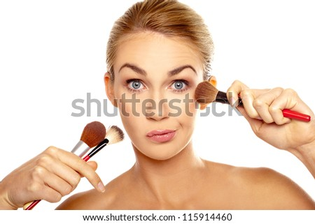 Humorous image of woman with an array of makeup brushes in her hand pulling a face as she realises she does not have any idea which one to use - stock photo