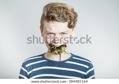 Humorous Nutrition Concept Image - Head and Shoulders Portrait of Frowning Boy with Wavy Blond Hair with Mouth Full of Mixed Salad Lettuce Greens in Studio with White Background and Copy Space - stock photo