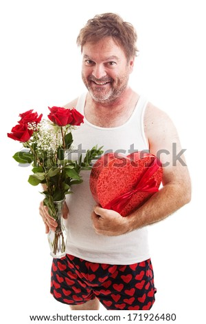 Humorous photo of a scruffy looking middle aged man in his underwear holding a bouquet of roses and a box of Valentines day candy for his sweetie. Isolated on white.
