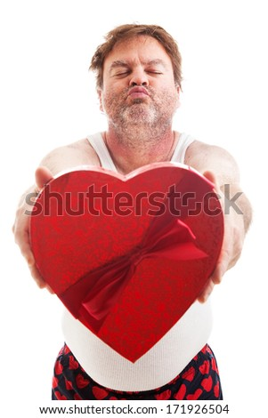 Humorous photo of a scruffy looking middle aged man in his underwear holding a box of Valentines day candy and waiting for a kiss. Isolated on white. - stock photo