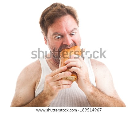 Humorous photo of a scruffy unshaven man in his undershirt, eating a big submarine hoagie sandwich.  Isolated on white.
