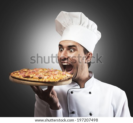 Humorous portrait of a male chef with opened mouth looking at pizza, gray background - stock photo