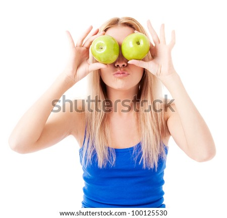 humorous portrait of a  young woman  holding two apples, isolated against white background - stock photo
