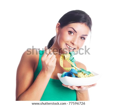 humorous portrait of a young woman keeping a diet and eating measuring tapes