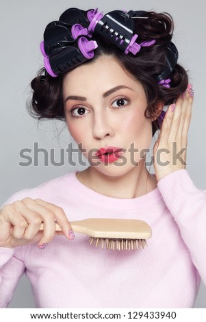 Humorous portrait of young beautiful woman with hair curlers and brush